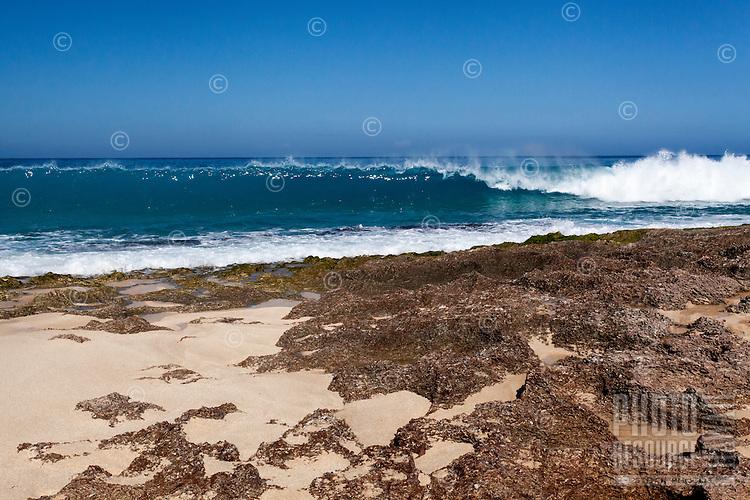 Wave breaking along a rocky shoreline at Keiki Beach, North Shore, O'ahu.