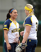Michigan Wolverines shortstop Sierra Romero (32) talks with pitcher Megan Betsa (3) during the season opener against the Florida Gators on February 8, 2014 at the USF Softball Stadium in Tampa, Florida.  Florida defeated Michigan 9-4 in extra innings.  (Copyright Mike Janes Photography)