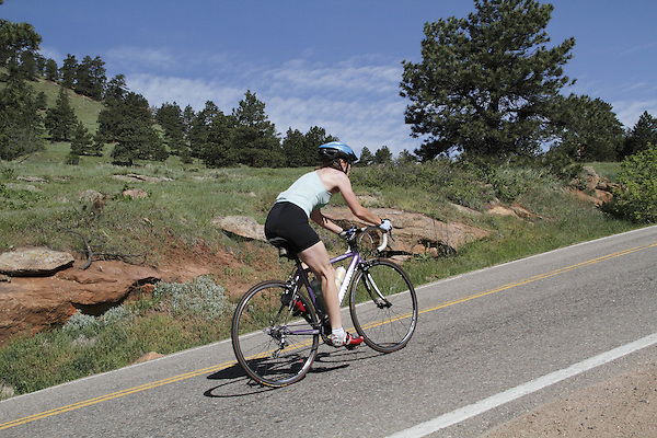 Caucasian female biking uphill on Lookout Mountain Road west of Denver, Colorado, USA .  John leads private photo tours in Boulder and throughout Colorado. Year-round.