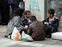 Pictured L-R: Afghan widow and mother of five Karima, 35 with three of her children, Samar, 5 and Fahad, 7 and Saud, 9 eat at a street corner Tuesday 08 March 2016<br />Re: Migrants at Victoria Square, in central Athens, Greece.