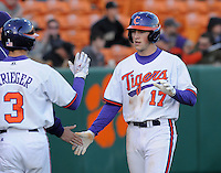 Steve Wilkerson (17) of the Clemson Tigers is congratulated after scoring a run in the seventh inning of a game against the Wofford Terriers on Wednesday, March 6, 2013, at Doug Kingsmore Stadium in Clemson, South Carolina. Clemson won, 9-2. (Tom Priddy/Four Seam Images)