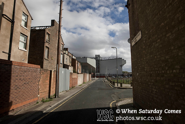 Boarded up and derelict houses in a street adjacent to Anfield, home of Liverpool football club, with the Kop stand pictured in the background. The club was one of the most successful and best supported teams in England and which won many domestic and European trophies. The most-famous part of the stadium was the Kop, where the Liverpool fans sat during games. Photo by Colin McPherson