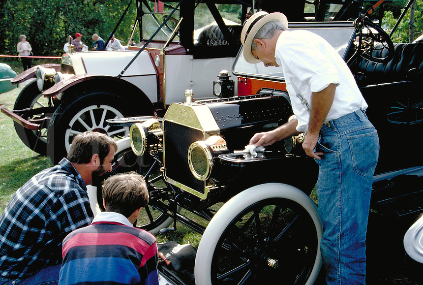 A man polishes a 1913 Ford Model T at a classic-antique auto meet. nostalgia, automobiles, vintage, collectors, cars. Vermont.