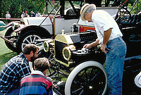 A man polishes a 1913 Ford Model T at a classic-antique auto meet. nostalgia, automobiles, vintage, collectors, cars. Vermont.