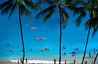 Tourists swimming in blue ocean waters at Waikiki beach with palm trees