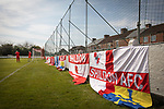 Shildon 0 Warrington Rylands 0 (4-5 pens), 17/04/2021. Dean Street, FA Vase Fourth Round. Home club flags on display around the perimeter fence as players warm-up before Shildon take on Warrington Rylands in an FA Vase Fourth Round tie at Dean Street. Formed in 1890, the home club are members of the Northern League Division One with their rivals playing in the North West Counties League Premier Division. The away team won the match 5-4 on penalties after a 0-0 draw over 90 minutes, in a fixture played without spectators permitted due to ongoing Covid-19 restrictions. Photo by Colin McPherson.
