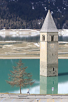 21st April 2021; Imst, Austria;  Cycling Tour des Alpes Stage 3,  Imst in Austria to Naturns/Naturno, Italy; A jogger runs close to the beautiful Resia lake and Bell tower