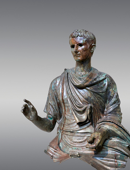 Roman bronze statue fragment of emperor Augustus, Circa 12-10 BC,  found in the Agean sea of  the Island of Euboea, Athens National Archaeological Museum. cat no X 23322. Against grey.<br /> <br /> The emperor Augustus is depicted in mature age mounting a horse. He wears a tunica with verivle purple stripes (clavus purpurea) fringed with a meander pattern. Icongraphic features of bthe Prima Porta and Actuim type of statue are incorporated in this brnze statue. The right hand is raised in a gesture of offical greeting and the left hand held the horses reigns. A ring on the finger gears has engraved the symbol of Pontifles Maximus assumed by Augustus in 12 BC