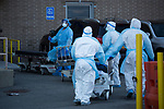 Healthcare workers wheel hospital beds after transporting deceased people to a refrigerated trailer serving as a temporary morgue outside of Wyckoff Heights Medical Center during the coronavirus pandemic in the Brooklyn borough of New York, the United States, Monday, April 6, 2020.  More than 10,000 people have died from COVID-19 in the U.S..  (Xinhua/Michael Nagle)