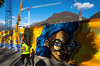 """Switzerland. Canton Ticino. Lugano. Cranes and construction site. Graffitis. Topic: """"Creative Freedom"""". Street art work commissioned by USi (Università della Svizzera italiana) and SUPSI (Scuola universitaria professionale della Svizzera italiana) on the construction's walls on the new campus which will be open in the autumn of 2020. The work was done by the artists: OThe USB plugs by Daniel Zellner (Left)- A smiling woman with blue hair by Kler e SofreeSo (Right). A woman jogs on the sidewalk. 27.10.17  © 2017 Didier Ruef"""