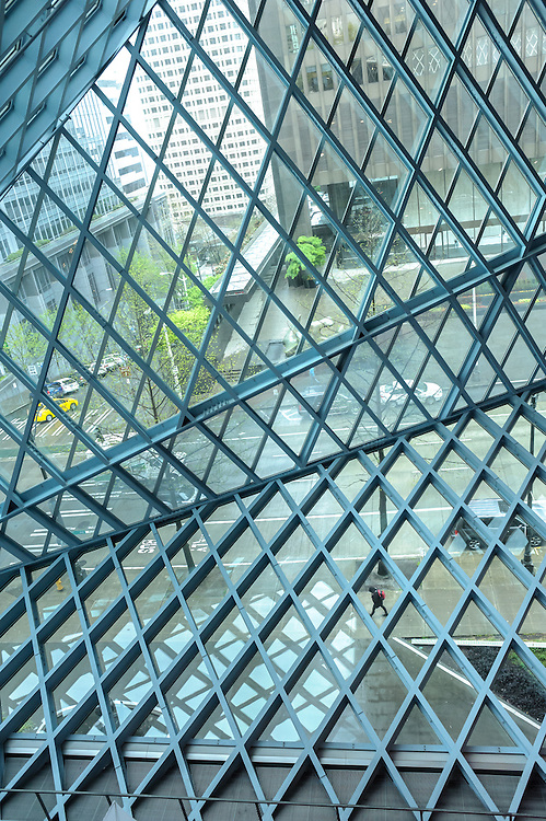 An individual walks through a pattern of steel.  Seattle Central Public Library
