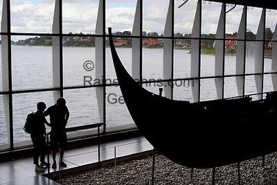 Denmark, Zealand, Roskilde: Viking age ship inside the Viking Ship Hall at the Viking Ship Museum with Roskilde Fjord behind | Daenemark, Insel Seeland, Roskilde: Ueberreste eines Vikingerschiffs im Wikingerschiffmuseum