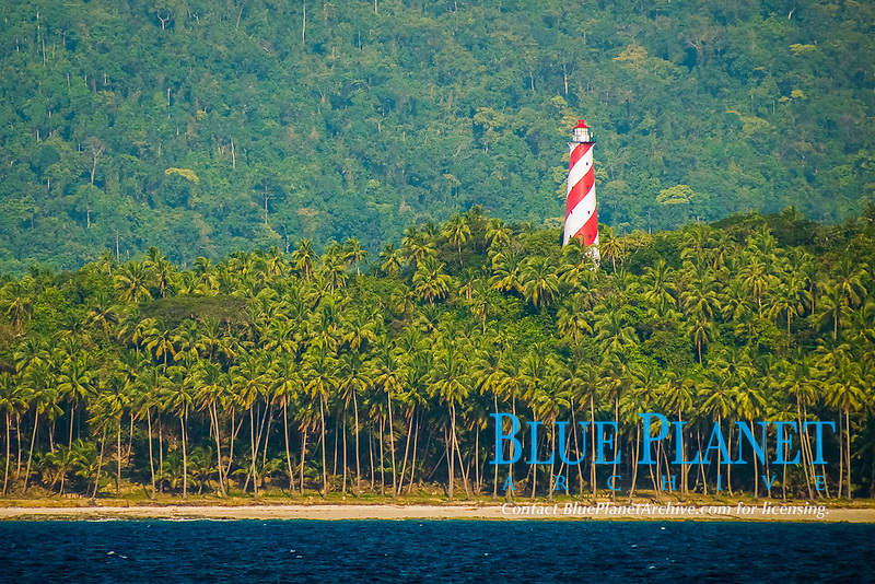 This candy-cane striped lighthouse stands out against the backdrop of coconut trees and primary rainforest, a key landmark for vessels arriving in Port Blair. Andaman Islands, Andaman Sea, India