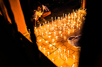An Afro-Colombian Catholic follower lights a candle while taking part in a religious procession during the San Pacho festival in Quibdó, Colombia, 4 October 2019. Every year at the turn of September and October, the capital of the Pacific region of Chocó holds the celebrations in honor of Saint Francis of Assisi (locally named as San Pacho), recognized as Intangible Cultural Heritage by UNESCO. Each day carnival groups, wearing bright colorful costumes and representing each neighborhood, dance throughout the city, supported by brass bands playing live music. The festival culminates in a traditional boat ride on the Atrato River, followed by massive religious processions, which accent the pillars of Afro-Colombian's identity – the Catholic devotion grown from African roots.