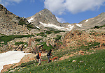 Couple hiking with dog along Mitchell Creek Trail, Mount Toll behind, Colorado. Guided photo tours to Indian Peaks. .  John offers private photo tours in Denver, Boulder and throughout Colorado. Year-round.