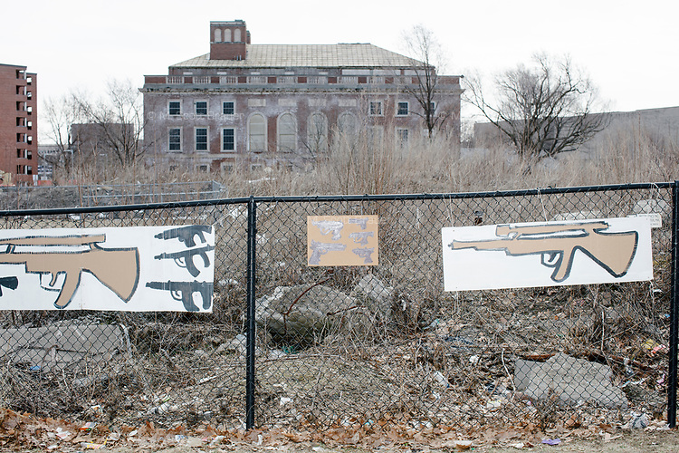 """Hand-drawn images of guns and signs reading """"8 children killed every day"""" hang on a fence near an abandoned building as people take part in the March For Our Lives protest, walking from Roxbury Crossing to Boston Common, in Boston, Massachusetts, USA, on Sat., March 24, 2018, in response to recent school gun violence."""