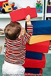 18 month old toddler boy stacking large foam blocks vertical