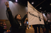 "Amanda Frank and other protesters hold a banner and raise four fingers in support of the ""Fairbanks Four"" during Governor Bill Walker's appearance at the 2015 Alaska Federation of Natives Convention at the Dena'ina Center."