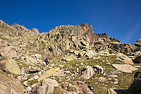 Parc National du Mercantour.  Hiker walks on track through the Vallee des Merveilles, GR52, Alpes-Maritimes, Provence, France. Model released.