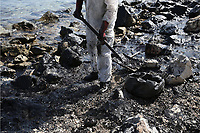 """Pictured: Specialist crew clean up the oil spill that has reached the coast of Salamina, Greece<br />Re: An oil spill off Salamina island's eastern coast is spreading and has become """"an environmental disaster"""" according to local authorities in Greece.<br />The spill was caused by the sinking of the Aghia Zoni II tanker, carrying 2,200 metric tons of fuel oil and 370 metric tons of marine gas oil on Saturday, southwest of the islet of Atalanti near Psytalleia. According to reports, the coastline stretching from Kinosoura to the Selinia community has """"turned black"""" and authorities fear a new leak from the sunken ship.<br />According to the island's mayor, Isidora Papathanasiou, the weather """"turned on Sunday afternoon and brought the oil spill to Salamina."""""""