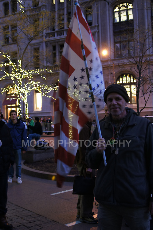 Al Burgo, Protestor carrying an interesting flag resembling the American Flag.  OWS/ Occupy Wall Street 25th of November 2011