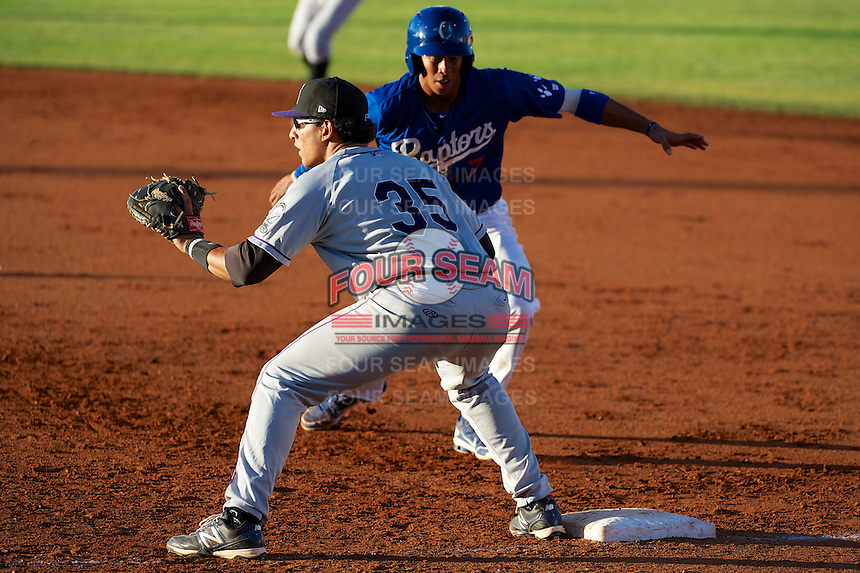 Grand Junction Rockies Jose Briceno #35 waits for the throw as Ogden Raptors Jacob Scavuzzo #7 races back to the bag in Pioneer League action at Lindquist Field on June 27, 2013 in Ogden, Utah. (Stephen Smith/Four Seam Images)