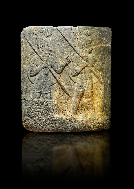 Photo of Hittite relief sculpted orthostat stone panel of Herald's Wall. Limestone, Karkamıs, (Kargamıs), Carchemish (Karkemish), 900-700 B.C. Military parade. Anatolian Civilisations Museum, Ankara, Turkey.<br /> <br /> Three helmeted soldiers in short skirts carry the shield on their backs and the spears in their hands. The bottom right part of the relief was left untreated since the pedestal stood in front of it. <br /> <br /> Against a black background.