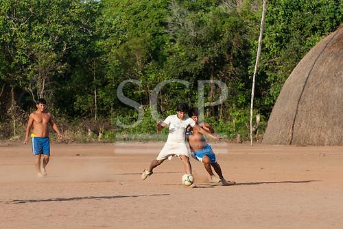 Xingu Indigenous Park, Mato Grosso, Brazil. Aldeia Matipu. Indigenous men playing in a football match.