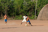 Xingu Indigenous Park, Mato Grosso, Brazil. Aldeia Matipu. Indigenous men playing in a football match.