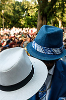 Two men in stylish hats in intimate conversation at Charlie Parker Jazz Festival, Tompkins Square Park, New York City, August 2019