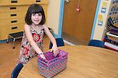 MR / Schenectady, NY. Zoller Elementary School (urban public school). Kindergarten classroom. Student (girl, 5) fitting nesting baskets inside each other. MR: Coh2. ID: AM-gKw. © Ellen B. Senisi.