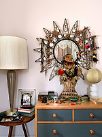 A wicker torso and a retro metal-framed mirror are used to display a collection of jewellery