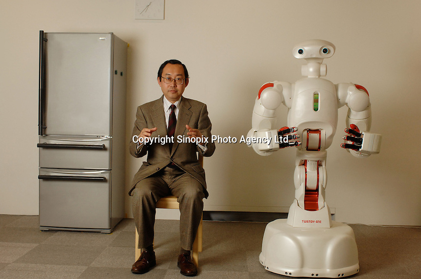 """Professor Shigeki Sugano, head of the Department of Modern Mechanical Engineering at Tokyo's Waseda University, poses next to Twendy One. The human symbiotic robot """"Twendy One"""" that is being developed to aid in labor shortage and in aging societies. The 1.5 meter tall and 111 kg heavy robot is able to assist lift a human and also is dextrous enough to massage."""
