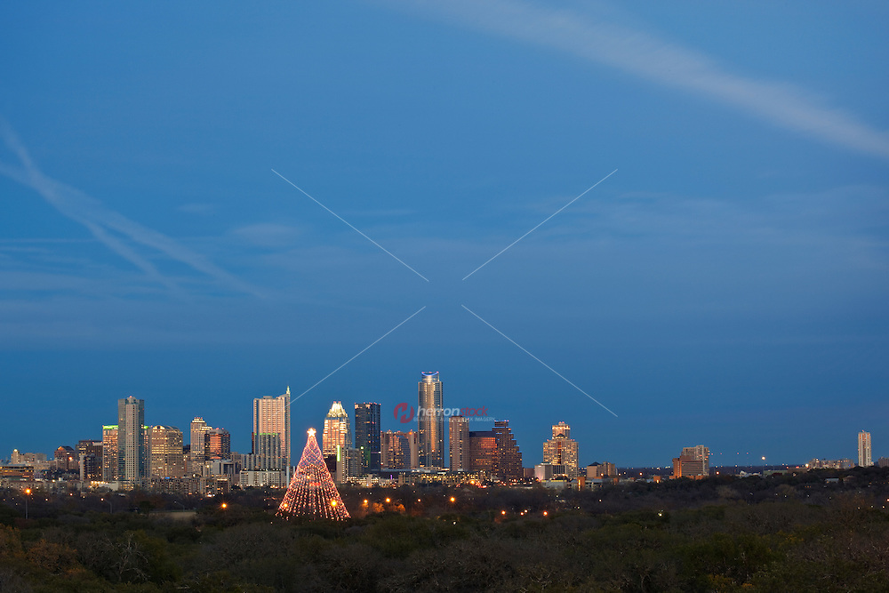Zilker Tree Holiday Festival at Zilker Park shines bright against the downtown Austin, Skyline