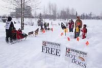 Josh Cadzow runs past a sign for free hotdogs courtesy of Horizon Lines along the bike trail near the Alaska Native hospital during the Ceremonial Start of Iditarod 2012 in Anchorage, Alaska.