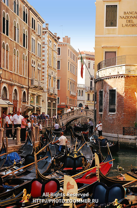 Many colorful empty gondolas in Venice canal with gondolier and bridge on background