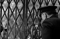"""Tournage du film """"La Bourse ou la Vie"""" de Jean Pierre Mocky, dans le quartier de St Sernin, Tououse, France, novembre 1965<br /> <br /> 2 novembre 1965. Gros plan sur la grille refermée par un gardien (un acteur) regardant au travers l'acteur Fernandel, lors du tournage <br /> <br /> PHOTO:  Fonds André Cros,"""