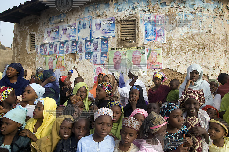 A crowd of children and women watch a spectactular parade of horsemen, musicians and people at the Kano Durbar. This celebrates the Muslim festival of Eid al-Adha and is the time for the populace to pledge their loyalty to their traditional ruler, the Emir of Kano.