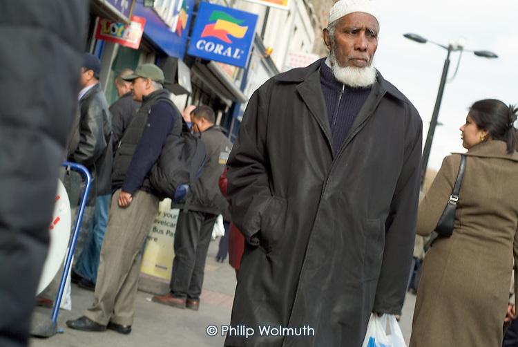 An elderly Bangladeshi man walks through Whitechapel Market, in the London Borough of Tower Hamlets.