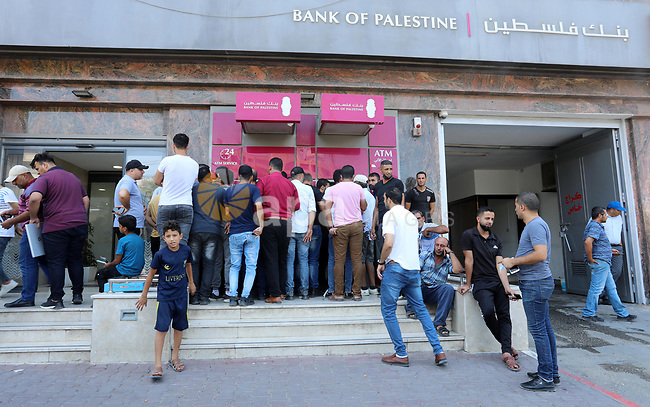 Palestinian Authority employees wait outside banks to receive their salaries, in Gaza city on August 10, 2021. Palestine is facing a financial crisis amid a decline in foreign aid and a growing tax dispute with Israel. The Palestinian government, which used to pay its employees before the fifth of every month, is still unable to pay the salaries for July. Photo by Ashraf Amra