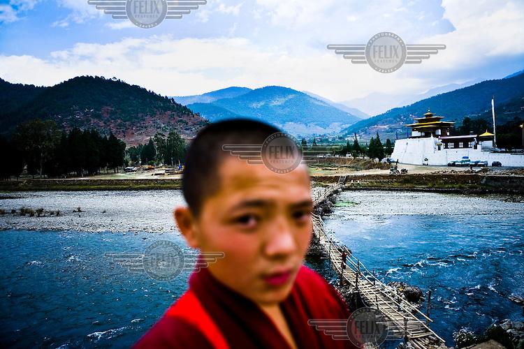 Young Buddhist monks next to the Pho Chhu river next to the Punakha dzong in Punakha, Bhutan.