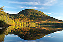 Cannon Mountain reflected in the still water of Lonesome Lake in early autumn.