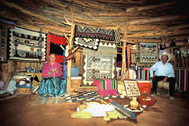 Navajo weaver, with her husband, spins wool as she sits next to her weaving loom and traditional rugs hang that are for sale inside her hogan at Monument Valley
