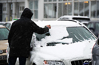 UK Weather: Heavy flurries of snow fall in Aberystwyth, west Wales,  on a cold February morning in Aberystwyth, west Wales, UK. Tuesday 06 February 2018.  A man clears his car windscreen of snow before his journey<br /> The Met Office has issued a 'yellow' warning for snow and ice, as a band of sleet and snow moves in from the west, to cover much of Wales and the north of England