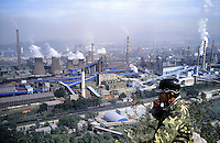 A worker sits on the hill above the factory of Benxi Iron and Steel Group in Liaoning. China's second-largest steelmaker Anshan Iron & Steel Group has merged with smaller rival Benxi Steel Group to create a company with capacity that will match the mainland's biggest steelmaker, Shanghai Baosteel Group..02 Sep 2005
