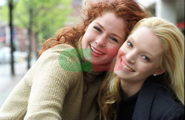portrait of two smiling women in early 20's cheek to cheek