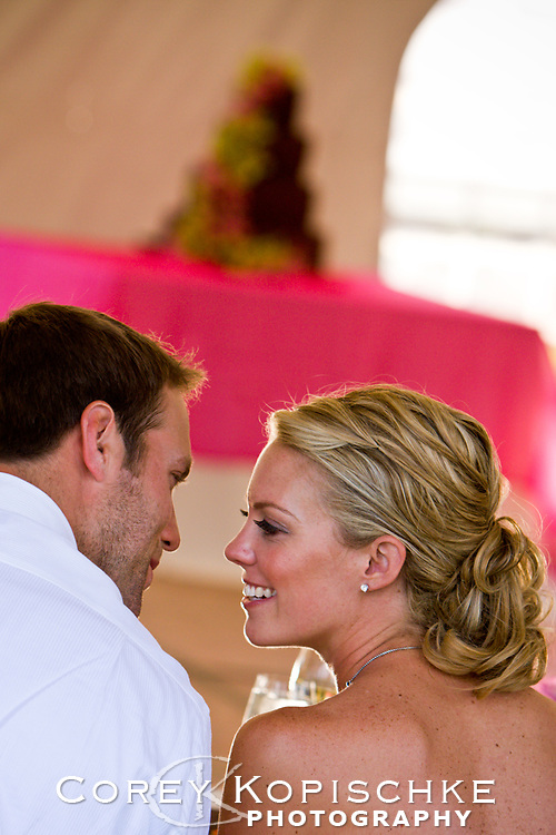Bride and groom before a kiss at the reception table.