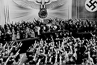 """Berlin, March 1938 - Title: Hitler accepts the ovation of the Reichstag after announcing the """"peaceful"""" acquisition of Austria. It set the stage to annex the Czechoslovakian Sudetenland, largely inhabited by a German-speaking population."""