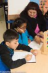 Afterschool homework help program for Headstart graduates Grades K-3 female teacher working with first grade students, math activity