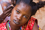 Fatimata Diallo comes from Eastern Burkina Faso, but has traveled to the capital, Ouagadougou, to visit relatives.  She takes the opportunity of a brief respite from cooking and laundry to get her hair braided.  Fatimata bears the traditional facial scarring and black lip tattoos of the Fulani people.